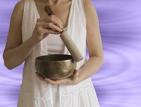 pic of tibetan  - Female Sound Healer using Tibetan Singing Bowl with sound wave effect in background - JPG