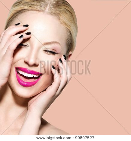 Laughing Beautiful Young Woman with Clean Fresh Skin close up over beige background. Beauty Portrait