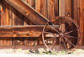 stock photo of wagon wheel  - Old western metal rusty wagon wheel leaning up against an old wooden brown barn door - JPG