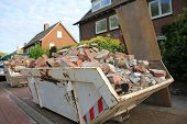 picture of dumpster  - Loaded dumpster near a construction site home renovation