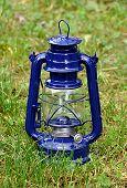 pic of kerosene lamp  - Detailed view of the blue kerosene lamp in the grass - JPG