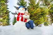 foto of snowman  - Girl and snowman with scarf and hat together during sunny winter day in the forest - JPG