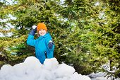 picture of snowball-fight  - Happy boy in blue winter jacket playing snowballs behind the snow wall with forest on the background - JPG