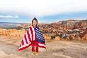 foto of bundle  - Laughing small boy with open mouth bundled up into American flag - JPG
