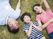 picture of love making  - little asian boy lying on grass making a wish with eyes closed while his parents looking at him affectionately - JPG