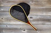 stock photo of trout fishing  - Landing net for trout fishing on rustic wooden boards - JPG