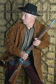 stock photo of gunslinger  - Mature male bandit with gun in the wild west  - JPG