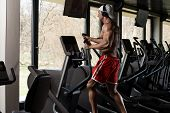 picture of elliptical  - Muscular Mature Man Doing Aerobics Elliptical Walker In Modern Fitness Center - JPG