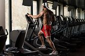 foto of elliptical  - Muscular Mature Man Doing Aerobics Elliptical Walker In Modern Fitness Center - JPG