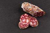 picture of salami  - slices of salami on a dark stone board as a background - JPG