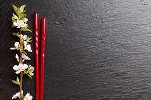 stock photo of sakura  - Japanese sushi chopsticks and sakura blossom on black stone background - JPG