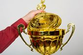 picture of plinth  - Hand opens the lid of the golden cup with a musical key - JPG