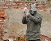 pic of nuclear disaster  - Man with gas mask and green military clothes explores dead bird after chemical disaster - JPG