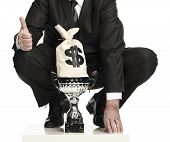 pic of money prize  - businessman with trophy money bag and doing the thumbs up sign isolated on a white background - JPG