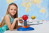 stock photo of geography  - Young girl study solar system in geography science class using a scale model - JPG