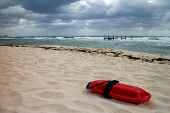 stock photo of lifeguard  - torpedo lifeguard buoys in the sand near the shore with stormy weather  - JPG