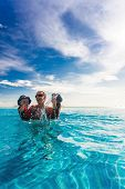 picture of infinity pool  - Happy family splashing in blue infinity  swimming pool of a tropical resort - JPG