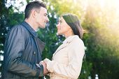 image of flirt  - Portrait of a beautiful couple flirting in park and looking at each other - JPG