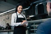 foto of apron  - Happy female waiter in apron writing order in restaurant - JPG