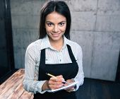 picture of apron  - Happy pretty female waiter in apron with notepad and pen in cafe - JPG