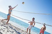 stock photo of volleyball  - Friends playing volleyball at the beach - JPG