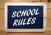 stock photo of slating  - The phrase School Rules in white text on a slate blackboard placed on a wooden surface - JPG
