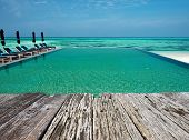 stock photo of infinity pool  - Swimming pool and old wooden pier in the tropical hotel - JPG