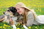 picture of shepherds  - A girl is laying outside in the grass tenderly hugging her aging German Shepherd mix dog with her eyes closed - JPG