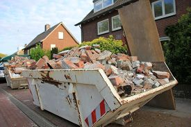 stock photo of dumpster  - Loaded dumpster near a construction site home renovation