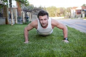foto of tantra  - An attractive man and woman practice tantra yoga on a grass before the house - JPG