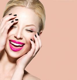 stock photo of touching  - Laughing Beautiful Young Woman with Clean Fresh Skin close up over beige background - JPG