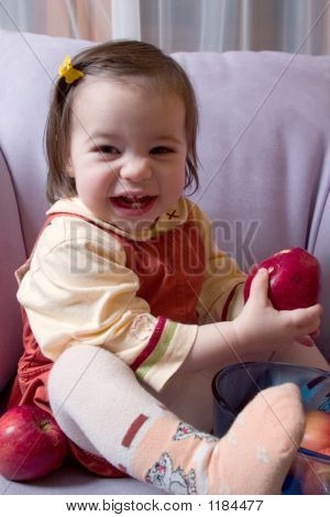 Picture or Photo of Little cute girl playing with apples sitting on the sofa and laughing