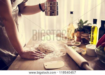 Woman preparing dough basis.Ingredients for baking.Female hands spilling powder on dough