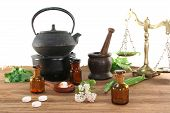 picture of naturopathy  - Pharmacists scale with mortar tea kettle bottle pharmacist and fresh herbs - JPG