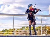 Постер, плакат: Music street performers girl violinist with blue hair playing aganist sky with clouds outdoor Free