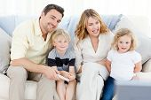 foto of happy family  - Adorable family watching tv in the living room - JPG