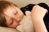 stock photo of have sweet dreams  - The child has a rest on a sofa with a toy in hands - JPG