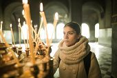 Постер, плакат: Young female lighting candles in a church during praying Yellow votive candles burning
