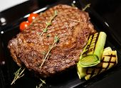 picture of ribeye steak  - Rib eye steak served on black plate with herbs and grilled vegetables - JPG