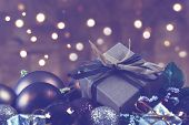 Shabby chic gift nestled in Christmas decorations with bokeh lights poster
