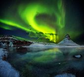 Kirkjufell mountain with beautiful aurora borealis and frozen water falls in winter, Iceland. One of poster