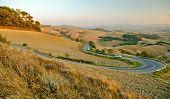 picture of twisty  - A twisty country road winding its way through the Tuscan countryside towards the hilltop town of Volterra - JPG