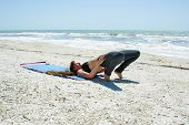 Woman Doing Yoga Exercise On Beach In Bridge Pose