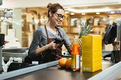 Smiling female cashier scanning grocery items at supermarket poster