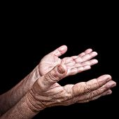 Wrinkled old hands begging isolated on a black background