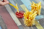 Hand Dipping French Fries In Ketchup. French Fries Serve In Two Glass Mugs On A Wooden Surface Paint poster
