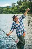 Fly Fisherman Using Fly Fishing Rod In Beautiful River. A Fisherman With Fishing Rod On The River. B poster