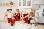 Cute Little Children In Red Pajamas, Preparing Cookies And Eats A Bred In The Kitchen At Home. Sits  poster