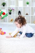 Sweet girl playing on floor in domestic room poster
