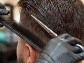 Stylists Hands In Black Rubber Gloves Cutting Hair With Scissors And Comb, Close Up View. Stylist At poster